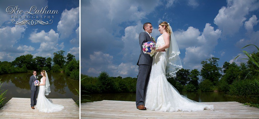 bride and groom by the lake beautiful blue skies